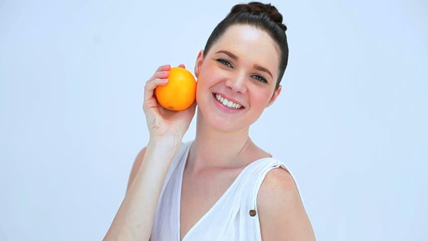 a girl holding an orange